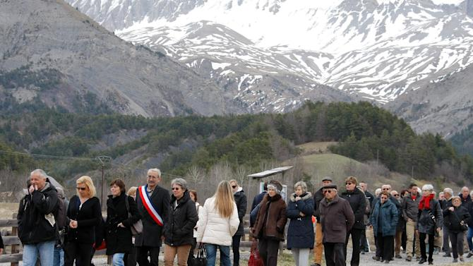 Inhabitants leave after an homage in front of a stele, a stone slab erected as a monument, set up in the area where a Germanwings aircraft crashed in the French Alps, in Le Vernet, France, Saturday, March 28, 2015. The crash of Germanwings Flight 9525 into an Alpine mountain Tuesday killed all 150 people aboard, and has raised questions about the mental state of the co-pilot. Authorities believe the 27-year-old German deliberately sought to destroy the Airbus A320 as it flew from Barcelona to Duesseldorf. (AP Photo/Claude Paris)