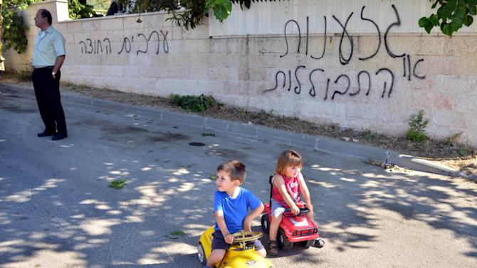 "FILE - An Israeli-Arab man and children are seen on a street next to Hebrew graffiti that reads, ""Racism or assimilation"" and ""Arabs out,"" in the village of Abu Ghosh near Jerusalem, June 18, 2013. In a land rife with religious tension, the village of Abu Ghosh has proven to be an exception, but that tranquility was briefly disturbed this week when Abu Ghosh became the latest victim in a wave of hate crimes that has plagued Israel, when unknown assailants slashed the tires of more than two dozen cars and sprayed anti-Arab graffiti. (AP Photo/Mahmoud Illean, File)"