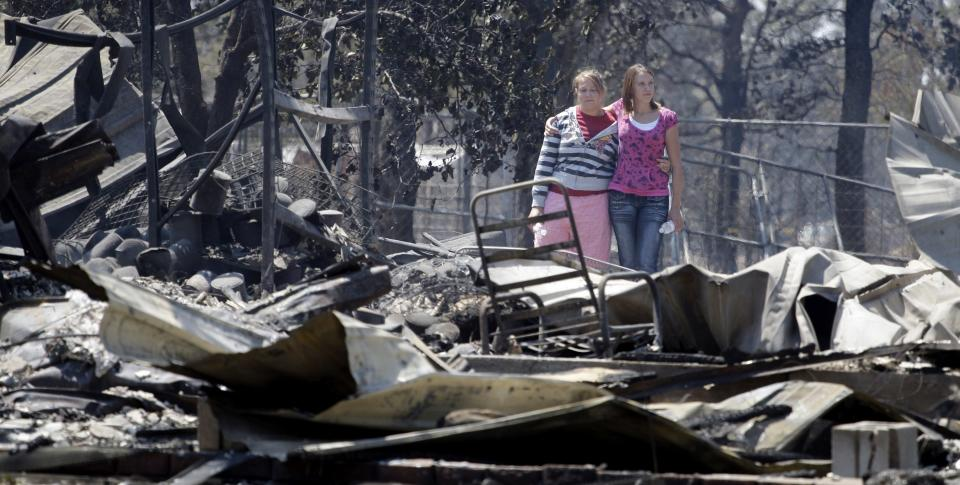 Sisters Laura, left, and Michelle Clements survey their fire-destroyed home, Tuesday, Sept. 6, 2011, in Bastrop, Texas. The Clements lost their home to fires Monday. (AP Photo/Eric Gay)