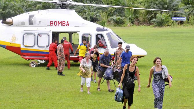Tourists are escorted out of a helicopter after they were evacuated from the National Park in Kuala Tahan to Jerantut