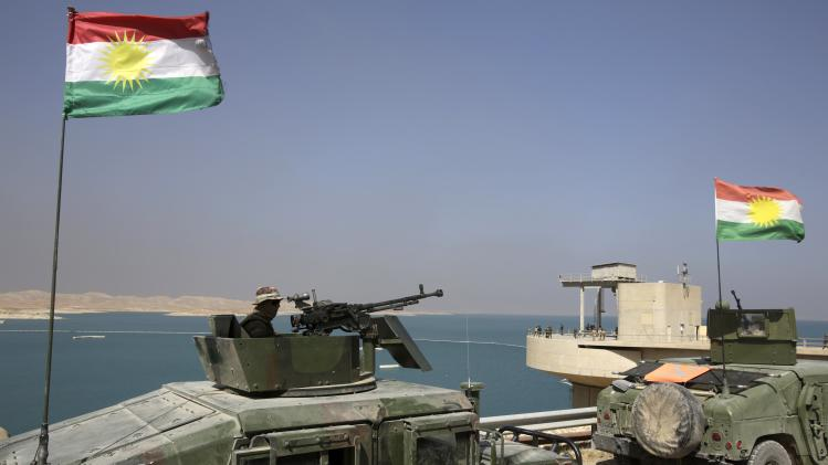 Peshmerga fighters are seen in vehicles with Kurdish flags as they guard Mosul Dam in northern Iraq