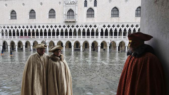 Masked revellers pose along the flooded St. Mark's Square during a period of seasonal high water and on the first day of carnival, in Venice