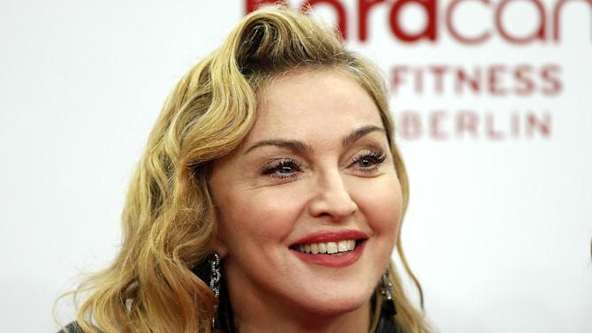 """In this Thursday, Oct. 17, 2013 photo, U.S. pop star Madonna smiles during her visit at the """"Hard Candy Fitness"""" center in Berlin. Madonna is in Haiti to visit humanitarian projects that her ex-husband Sean Penn has been overseeing since the Caribbean nation's devastating earthquake in 2010, Penn told The Associated Press Monday, Nov. 25, 2013. (AP Photo/Michael Sohn)"""