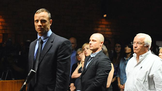 """FILE - In this photo taken Tuesday, Feb. 19, 2013 Olympian Oscar Pistorius stands following his bail hearing, as his brother Carl, center, and father Henke look on, in Pretoria, South Africa. The family of Oscar Pistorius, the double-amputee Olympian charged with murdering his girlfriend, is feuding publicly about whether guns are a necessary protection against crime in South Africa. British newspapers quoted Pistorius' father, Henke Pistorius, as saying the family owned handguns for self-defense and suggesting that South Africa's government shares blame for """"white crime levels"""" in the country. In a statement Tuesday March 5, 2013 quoting the runner's uncle, Arnold Pistorius, the family subsequently distanced itself from the father's comments. (AP Photo/Masi Losi/Pretoria News) SOUTH AFRICA OUT"""