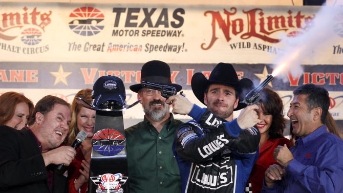 Track President Eddie Gossage, left, ducks as Jimmie Johnson (48) fires blanks out of a revolver as he celebrates in victory lane following his win in the NASCAR Sprint Cup Series auto race at Texas Motor Speedway, Sunday, Nov. 4, 2012, in Fort Worth, Texas. (AP Photo/Tim Sharp)