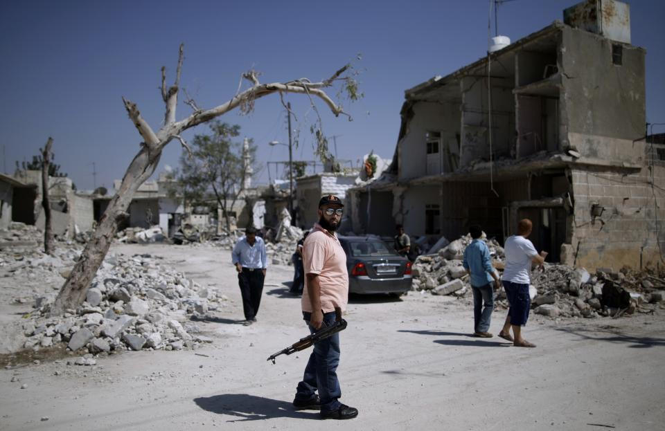 A Free Syrian Army soldier, center, looks on while he and other fighters check the area next to houses destroyed after Syrian government forces shelling, in Azaz, on the outskirts of Aleppo, Syria, Tuesday, Aug. 28, 2012. (AP Photo/Muhammed Muheisen)
