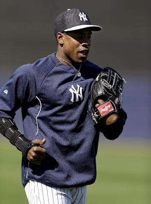FILE - In this March 26, 2013, file photo, New York Yankees center fielder Curtis Granderson, who is on the disabled list, wears a protective arm brace while working out in the outfield before a spring training baseball game against the Houston Astros in Tampa, Fla. Granderson has rejoined the Yankees on Tuesday, May 14, 2013, 2 and a half months after breaking an arm in his first at-bat of spring training. (AP Photo/Kathy Willens, file)