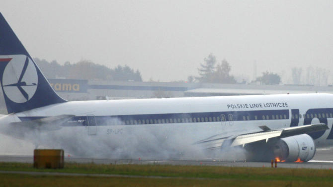 FILE - In this Tuesday, Nov. 1, 2011 file photo, a LOT airlines Boeing 767 makes an emergency landing at the Warsaw, Poland airport. The plane was en route from Newark with 230 people on board but no one was injured. Passengers on the plane that crash-landed in Poland when its landing gear failed to deploy have sued Boeing and the firm that inspected the airliner before it departed New Jersey, with one attorney saying his clients suffered severe emotional trauma from thinking they were about to die. A lawsuit claiming both physical and psychological damage was filed in November 2012 in Cook County Circuit Court in Chicago, where Boeing is headquartered, contends design flaws in the 767-300 led to fluid leaking from the hydraulic system. It said workers of New York-based Mach II Maintenance should have detected it. (AP Photo)