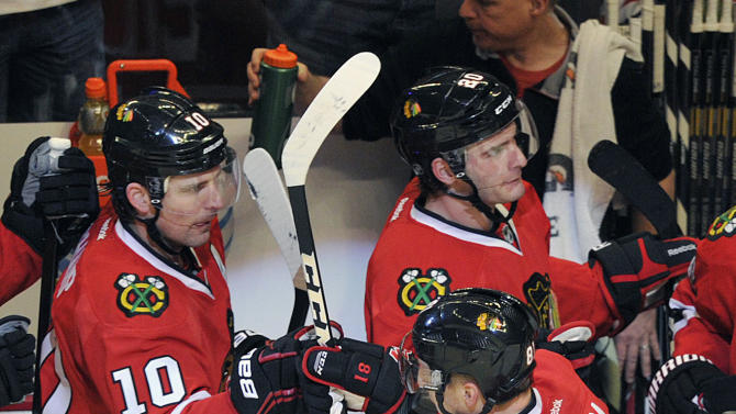 Chicago Blackhawks' Patrick Sharp (10) congratulates Marian Hossa (81) after Hossa's goal against the Minnesota Wild during the second period of Game 1 of an NHL hockey Stanley Cup playoff series Tuesday, April 30, 2013, in Chicago. (AP Photo/Jim Prisching)