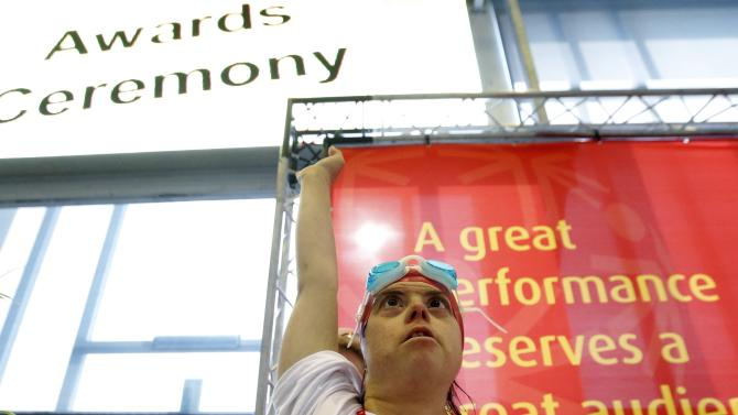 A athlete reacts on the podium during a swimming event at the 2014 Special Olympics Games in Antwerp