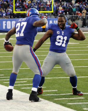 New York Giants defensive end Justin Tuck (91) celebrates after teammate Brandon Jacobs (27) scored a touchdown during the third quarter of an NFL football game against the Washington Redskins at New Meadowlands Stadium, Sunday, Dec. 5, 2010, in East Rutherford, N.J. The Giants won the game 31-7. (AP Photo/Bill Kostroun)