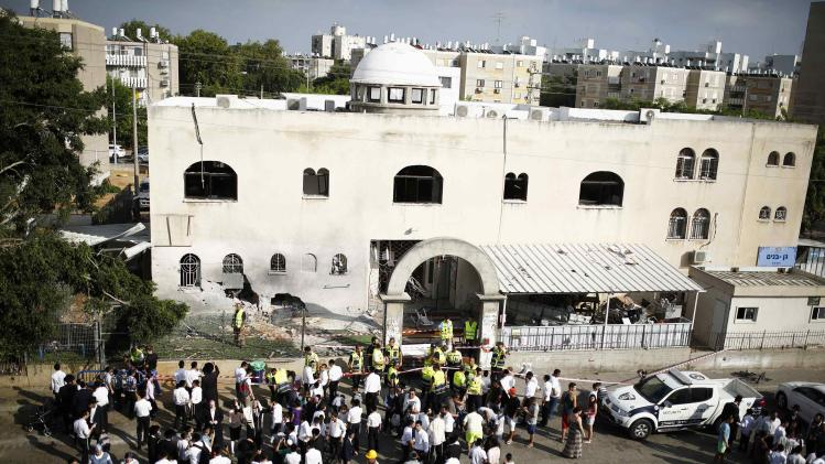 People stand next to a synagogue that was damaged by a rocket in the southern city of Ashdod