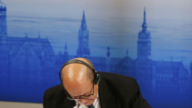 French Defence Minister Le Drian checks his papers at the Munich Security Conference in Munich
