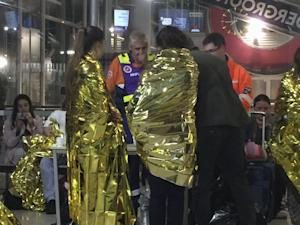Passengers wrapped in thermal foil blankets given out…