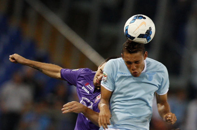 Fiorentina defender Nenad Tomovic, of Serbia, left, and Lazio forward Brayan Perea, of Colombia, jump for a header during a Serie A soccer match between Lazio and Fiorentina, at Rome's Olympic stadium