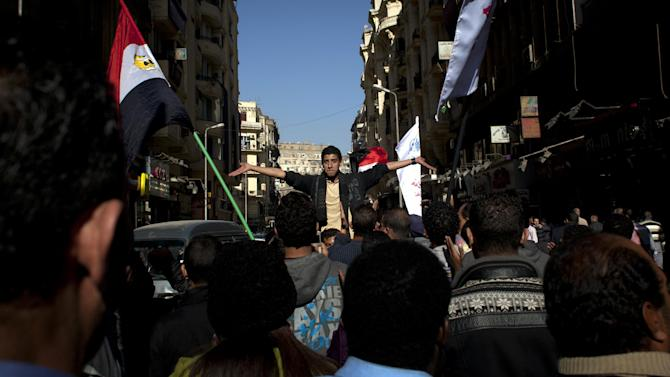 """Egyptian protesters chant slogans denouncing the proposed constitution and the upcoming referendum during a rally in Cairo, Egypt, Thursday, Dec. 13, 2012. Egyptian President Mohammed Morsi's Muslim Brotherhood and other Islamists have been plastering posters across much of the country urging Egyptians to vote """"yes"""" and listing what they call the advantages of the new charter. """"Yes, to protecting (Islamic) Sharia (laws),"""" says a Brotherhood website. The Islamists have also been using mosques to disseminate the """"yes"""" message and putting to use their appeal to uneducated Egyptians in rural areas. But the pros and cons of the draft constitution and the question of whether it will be passed have grown more akin to being a secondary narrative to the worst crisis to hit Egypt since the overthrow nearly two years ago of Hosni Mubarak's authoritarian regime. (AP Photo/Nasser Nasser)"""
