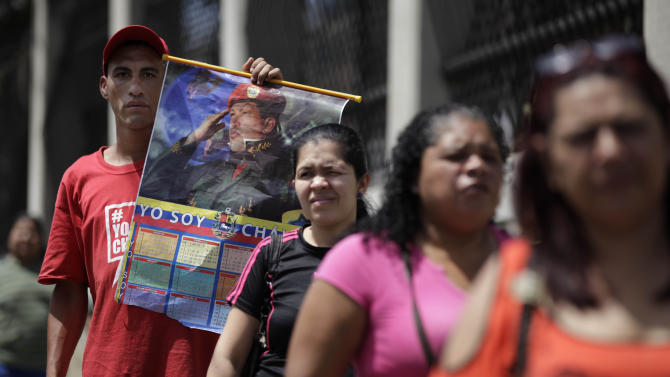 A supporter of Venezuela's President Hugo Chavez holds up a poster of Chavez behind people waiting in line to enter a military hospital in Caracas, Venezuela, Wednesday, Feb. 20, 2013.  Chavez is allegedly receiving treatment at this hospital, but the people in line are there for routine hospital visits unrelated to the president. Chavez's sudden return to Venezuela after more than two months of cancer treatments in Cuba has fanned speculation that the president could be preparing to relinquish power and make way for a successor and a new election. (AP Photo/Ariana Cubillos)