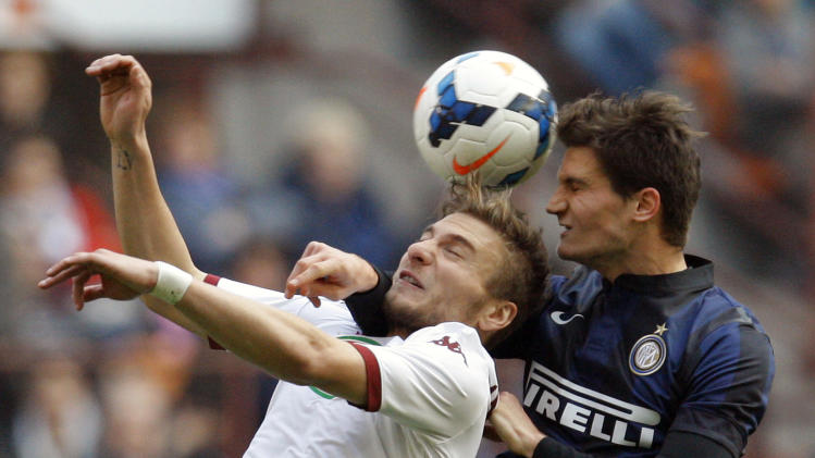 Inter Milan's Andreolli jumps for the ball against Torino's Immobile during their Italian Serie A soccer match in Milan