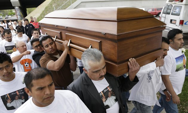 Mouners carry the casket of Ricardo Portillo along a street following a public wake to the funeral service at Our Lady of Guadalupe Church Wednesday, May 8, 2013, in Salt Lake City. People attended a funeral services to honor a Utah soccer referee who was punched by a player and later died after a weeklong coma. Portillo died Saturday, a week after police say a 17-year-old player struck him in the head during a recreational league soccer game after the referee called a penalty against him. (AP Photo/Rick Bowmer)