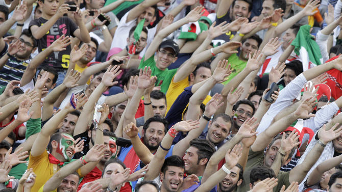 Iranian spectators, cheer, prior to start of Iran and Lebanon soccer match in their Asian qualifiers for 2014 World Cup, at the Azadi (Freedom) stadium in Tehran, Iran, Tuesday, June 11, 2013. Iran won the match 4-0. (AP Photo/Vahid Salemi)