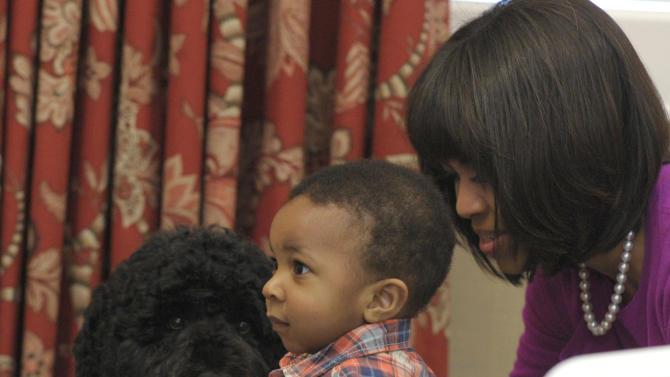 Anthony Robinson gets close to the Obama family dog, Bo, as first lady Michelle Obama watches during her visit to the Fisher House, located at Walter Reed National Military Medical Center in Bethesda, Md., Wednesday, March 20, 2013, for a pre-Easter celebration with military families and children. (AP Photo/Susan Walsh)
