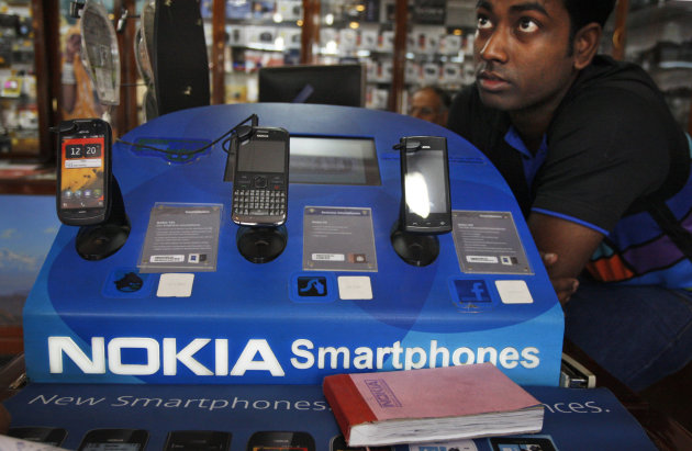 An Indian shopkeeper selling Nokia mobile phones awaits customers in New Delhi, India, Thursday, June 14, 2012. Nokia Corp. will lay off 10,000 jobs globally and close plants by the end of 2013, the company said Thursday, in a further drive to save costs and streamline operations.(AP Photo/Tsering Topgyal)