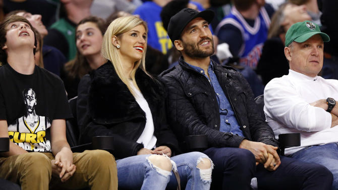 Boston Bruins' Patrice Bergeron, second from right, and his wife Stephanie look on from courtside during the second quarter of an NBA basketball game between the Boston Celtics and the Golden State Warriors in Boston, Sunday, March 1, 2015. (AP Photo/Winslow Townson)