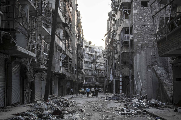 In this Saturday, Oct. 27, 2012 photo, Syrian residents walk on a street among the debris of buildings damaged by heavy shelling in the southeast of Aleppo City. (AP Photo/Narciso Contreras).