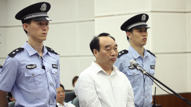 FILE - In this June 19, 2013 file photo, Lei Zhengfu, center, former Communist Party chief of Chongqing city's Beibei district, who was involved in a sex tape scandal, attends his trial on corruption charges, in a court in southwestern China's Chongqing city. The former Chinese official at the center of a sex scandal has been sentenced to 13 years in prison on Friday, June 28, 2013 for taking bribes of more than 3 million yuan ($510,000). (AP Photo, File) CHINA OUT