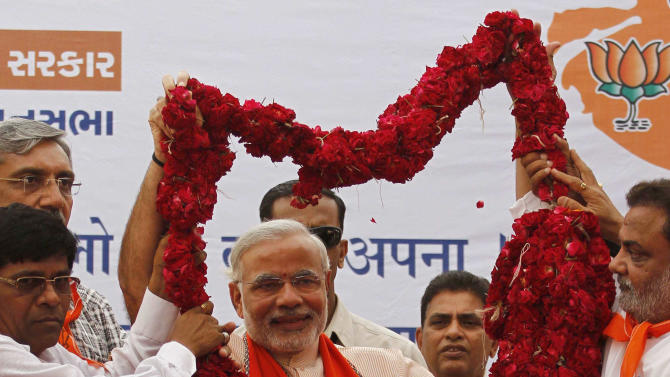 In this Nov. 30, 2012 photo, Gujarat Chief Minister Narendra Modi is presented with a garland of roses during a public meeting before filing his nomination for state assembly elections in Ahmadabad, India. Eleven years after Modi became the chief minister of the western state of Gujarat - and 10 years after brutal anti-Muslim rioting left over a 1,100 people there dead - Modi is campaigning for his third term. Nearly everyone expects him to be swept into office, and the top leadership of his rightwing Bharatiya Janata Party is already hailing him as a future prime minister. But few politicians in India are as polarizing as Modi. (AP Photo/Ajit Solanki)