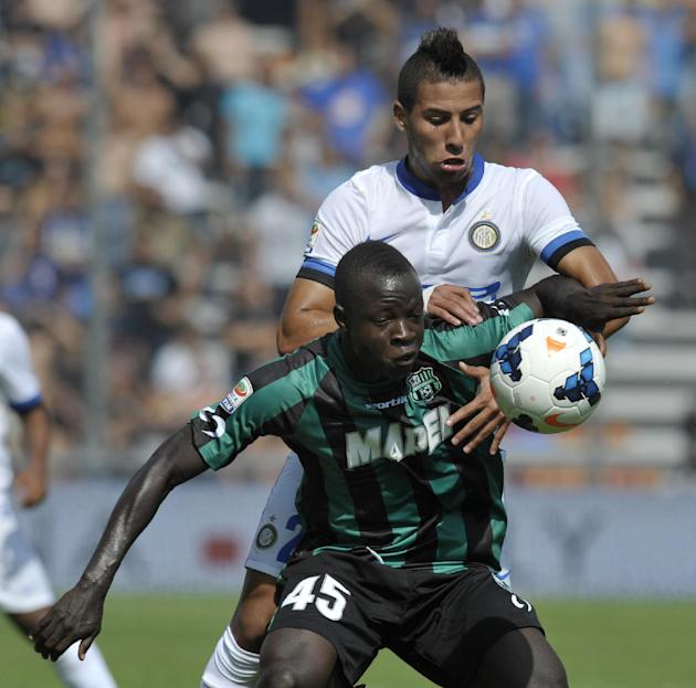 Sassuolo's Yussif Raman Chibsah, of Ghana, left, vies for the ball with Inter Milan's Saphir Taider, of Algeria, during their Serie A soccer match at Reggio Emilia's Mapei stadium, Italy, Sunday, Sept