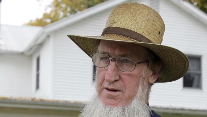 FILE - In this Oct. 10, 2011 file photo, Sam Mullet Sr. stands in the front yard of his home in Bergholz, Ohio. In the stern, self-regulating world of the Amish, those who act out time and again by wearing the wrong clothing, going to movies or otherwise flaunting the church's doctrine can find themselves utterly alone. At the root of Amish hair-cutting attacks in Ohio and the federal hate crime trial that followed, prosecutors say, was a dispute over religious differences and a decision by Amish bishops to overrule Mullet, the leader of a breakaway group who had shunned his former followers. (AP Photo/Amy Sancetta, File)