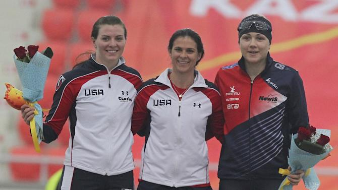 Winner Brittany Bowe of USA, center, celebrates on the podium with second place Heather Richardson of USA, left, and third place Karolina Erbanova of the Czech Republic after the women's ISU World Speed Skating Sprint Championship 500 meter event in Astana, Kazakhstan, Saturday, Feb. 28, 2015. (AP Photo/Alexei Filippov)