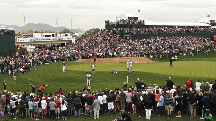 As crowds gather at the TPC Scottsdale, Phil Mickelson (wearing black), far right center, hits a putt on the 18th green during the final round of the Waste Management Phoenix Open golf tournament on Sunday, Feb. 3, 2013, in Scottsdale, Ariz. (AP Photo/Ross D. Franklin)