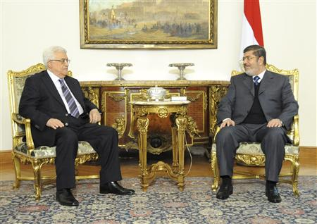 Palestinian President Mahmoud Abbas talks with Egyptian President Mohammed Mursi during their meeting in Cairo in this picture provided by the Egyptian Presidency