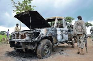 South Sudanese SPLA soldiers inspect a burned out car…