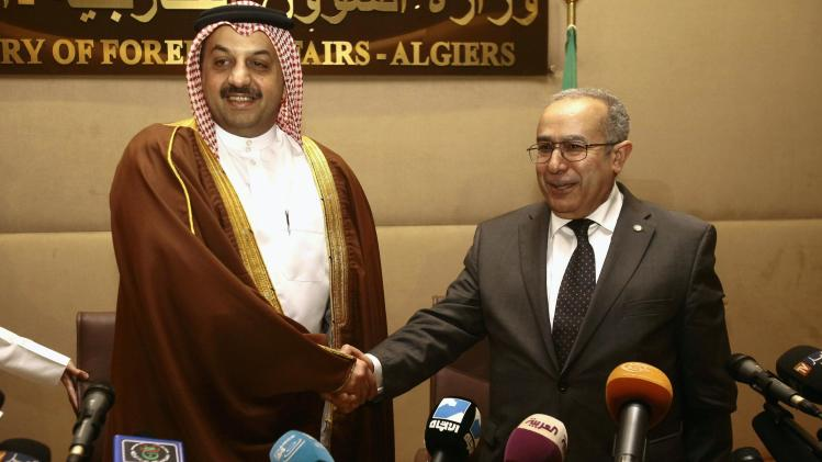 Khalid bin Mohamed al-Attiyah shakes hands with Lamamra after their joint news conference in Algiers
