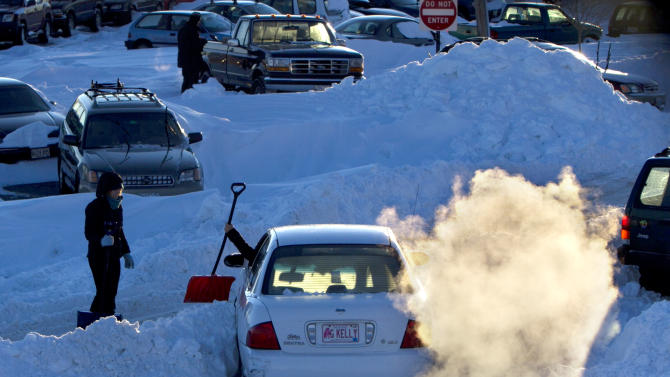Courtney Bazininet hands a shovel to her friend, Alice Fernald, after getting her car temporarily stuck in a snow bank, Sunday, Feb. 10, 2013, in Portland, Maine. Residents are digging out after a blizzard dumped a record 31.9 inches of snow on the city. (AP Photo/Robert F. Bukaty)