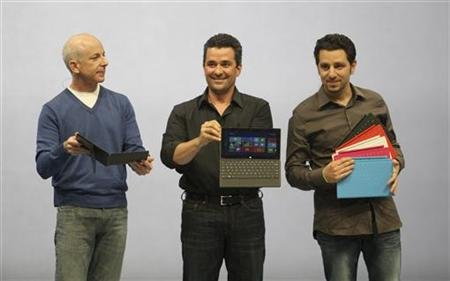 Steven Sinofsky, Michael Angiulo and Panos Panay hold the new Surface as it is unveiled in Los Angeles