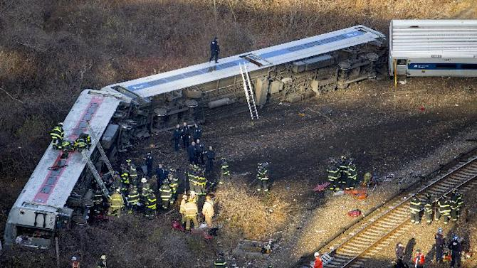 First responders work the scene of a derailment of a Metro-North passenger train in the Bronx borough of New York Sunday, Dec. 1, 2013. The train derailed on a curved section of track in the Bronx on Sunday morning, coming to rest just inches from the water and causing multiple fatalities and dozens of injuries, authorities said. Metropolitan Transportation Authority police say the train derailed near the Spuyten Duyvil station. (AP Photo/Craig Ruttle)