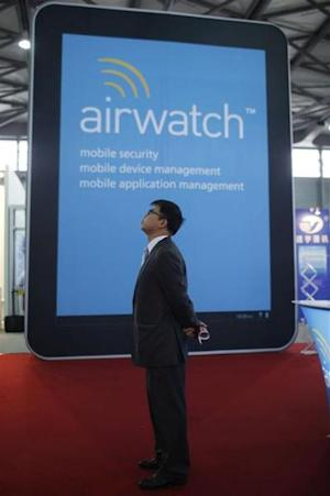 A man stands near an AirWatch display at the Mobile Asia Expo in Shanghai