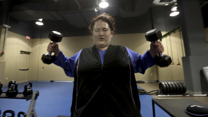 Ellen Hays works out during a morning exercise class at a gym in Addison, Texas,  Thursday, Jan. 3, 2013.   Downsize Fitness is a selective gym where the rule is that new members must tip the scales. New members are weighed and have their body mass index measured. (AP Photo/LM Otero)