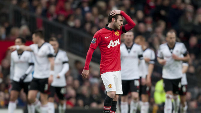 Manchester United's Juan Mata wipes his hair as Fulham players celebrate their first goal, scored by Steve Sidwell, during their English Premier League soccer match at Old Trafford Stadium, Manchester, England, Sunday Feb. 9, 2014. (AP Photo/Jon Super)