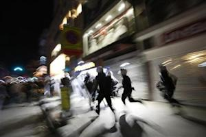 Riot police chase demonstrators during an anti-government protest in Istanbul's Kadikoy district