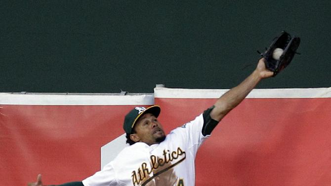 Oakland Athletics left fielder Coco Crisp makes a leaping catch on a ball hit by Detroit Tigers' Prince Fielder during the second inning of Game 3 of an American League division baseball series in Oakland, Calif., Tuesday, Oct. 9, 2012. (AP Photo/Ben Margot)