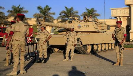"Egyptian army soldiers with a tank stand guard in front of the main gate at the Borg El Arab ""Army Stadium"" before the Egyptian Premier League derby soccer match between Al-Ahly and El Zamalek in the Mediterranean city of Alexandria"