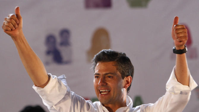 In this April 28, 2012 photo, Enrique Pena Nieto, presidential candidate for the Institutional Revolutionary Party (PRI), greets supporters during a campaign rally in Nezahualcoyotl, Mexico. If the next two months go as Pena Nieto plans, the PRI will return to Mexico's highest office after 12 years out of power, thanks to the tightly disciplined and highly professional political machinery of a 45-year-old candidate who has managed to push questions about his personal flaws, and the details of his plans for Mexico, to the background.  Mexico will hold presidential elections on July 1. (AP Photo/Marco Ugarte)