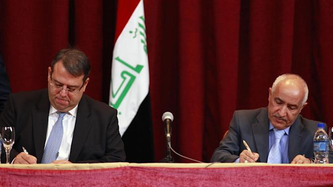 Gati Al-Jebouri, left, Executive Director of LITASCO LUKOIL global trader and Dhiya Jaafar, chief of Iraq's South Oil Company sign a contract  in Baghdad, Iraq, Wednesday, Nov. 7, 2012. A senior Iraqi oil ministry official says U.S. oil giant Exxon Mobil has expressed an interest in pulling out of a major oil field development project in the country's south. The comments by the ministry's licensing and contracts chief, Abdul-Mahdi al-Ameedi, mark the first official confirmation of Exxon's desire to exit the 8.6 billion barrel West Qurna Phase 1 project. (AP Photo/Hadi Mizban)