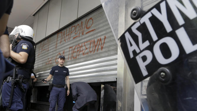 """Riot police stand by as a man ducks under lowered shutters at the entrance of the finance ministry, in Athens on Thursday, Oct. 11, 2012. Writing on the shutters reads: """"We won't pay. This will not pass."""" High school children protested outside the ministry Thursday against state funding cuts to municipalities that have disrupted school bus services. Greece's coalition government is struggling to meet demands by international rescue creditors for a massive new austerity cuts required for continued payment of emergency loans.   (AP Photo/Dimitri Messinis)"""