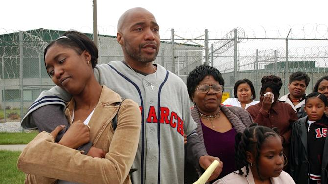 FILE - In this April 17, 2012 file photo, Terry Harrington, center, stands with his daughter Nicole Brown, left, his mother Josephine James, right, and family and friends outside the Clarinda Correctional Facility in Clarinda, Iowa, after Gov. Tom Vilsack signed his reprieve. Harrington and Curtis McGhee, wrongfully convicted in the 1977 murder of a retired Iowa police officer, hope to prove during a trial that starts Wednesday, Oct. 31, 2012, that officers coerced witnesses into fabricating testimony that framed them for killing John Schweer. (AP Photo/Charlie Neibergall, File)